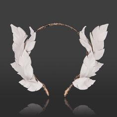 Luxe, handcrafted white leather leaf crown on a silk wrapped headband. A fashion forward statement for this year's Spring Racing Carnival.