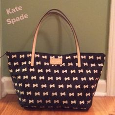 """Kate Spade Tuxedo Carryall Shoulder Bag Pre-loved Kate Spade Carryall in the Signature Bow design. Outside is a nylon and inside a pika-dot cloth. Zip closure, dual leather shoulder straps w/10"""" drop. Leather KS logo plate on front also one in the interior. Polka-dot cloth interior with zip pocket (small stain at bottom has shown in 3rd pic) and 2 slip pockets. I used this as an extra work bag and it can store a lot!!!  18""""x11""""x6"""". Price reflects. kate spade Bags Shoulder Bags"""