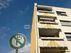 Beigefarbene sanierte Fassade eines Wohnhaus mit grünem Verkehrszeichen und blauem Himmel in Großauheim in Hessen
