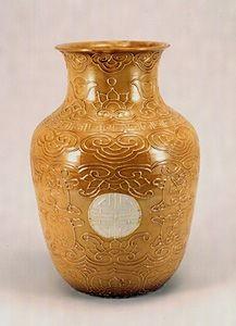 偕楽園焼 交趾写黄白釉寿字文花生 江戸時代後期 陶磁器 口径13.4cm,高さ29.7cm 1口  偕楽園焼の典型的な交趾写花生のスタイルで、文様の構成も同じであるが、外面の「壽」字の部分のみ白釉とし、その他の部分は黄釉で染めている点が珍しい。ただし、釉薬が薄いため、轆轤による調整痕を観察できる。また、浮き彫りとなっている文様線は、強く浮き出ており、一般的な二彩の作品より、文様の輪郭をはっきりと見ることができる。底面には、陰印刻銘で「偕楽園製」とある。