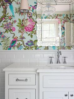 fabulous girl's bathroom features upper walls clad in turquoise birds and flowers wallpaper, Cole and Son Fontainebleau Wallpaper, and lower walls clad in white beveled subway tiles lined with a curved vanity fitted with an oval sink and vintage style faucet under a venetian mirror illuminated by Thomas O'Brien Bryant Sconces.
