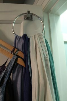 An old trick, but a good one: towel ring works perfectly to hold scarves on the closet door.  With two of us sharing this tiny closet, every bit of space is valuable.