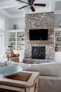 Home of the Month: Lake House Reveal Stone fireplace open shelving cozy coastal open living area. gray and white coastal living room. Fireplace Built Ins, Home Fireplace, Fireplace Remodel, Living Room With Fireplace, Fireplace Design, Fireplace Stone, Fireplace Ideas, Farmhouse Fireplace, Built In Shelves Living Room