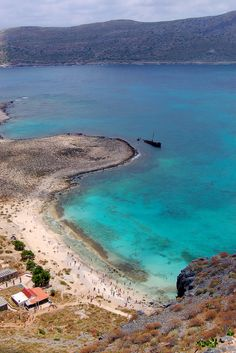 View of the beach from the Gramvousa fortress near the coast of the Greek island of Crete_ Greece | A sunken ship rests off the point of the popular swimming beach below the ruins of the Venetian fortress of Gramvousa.