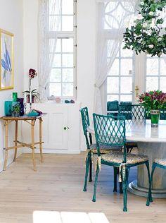 bleached floors, turquoise chinoiserie chairs, industrial spool-type table topped with marble...this space reminds me of an orangerie in Palm Beach