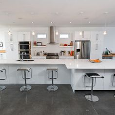 Modern White Kitchen with glass pendants and polished concrete floors