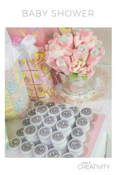 A grey and pink baby shower complete with a diaper cake, diaper bouquet, headband bar, and onesie banner.