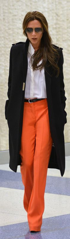 Office / work outfit: orange pants white blouse black coat Beckham touched down at JFK airport in orange trousers, a black military jacket and aviator shades. Mode Victoria Beckham, Victoria Beckham Fashion, Victoria Beckham Outfits, Orange Hose, Orange Yellow, Orange Color, Pantalon Orange, Vic Beckham, Black Military Jacket