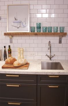 Grey cabinets with brass pulls.