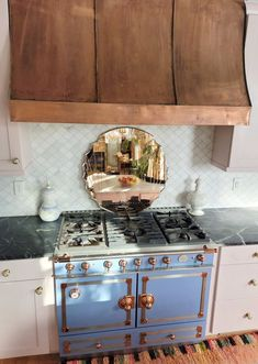 Copper Hood by popular CO home design blog, Eclectic Twist: image of a copper hood hanging above a blue gas range stove in a kitchen with pink cabinets, black and white marble countertop, white tile backsplash, and pendant lighting.