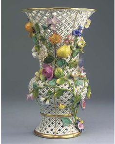A Meissen porcelain fruit- and flower-encrusted ajour beaker vase -   CIRCA 1860, BLUE CROSSED SWORDS MARK -   The basket-woven body enhanced in gilt and applied with branches (chips)  34 cm. high
