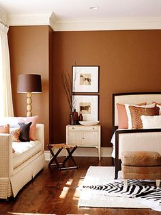 Eclectic Flair - A mix of exotic accents, including a faux-zebra rug, leopard-print pillows and crocodile-look leather ottomans, give this bedroom a modern look/feel. A warm brown hue on the walls looks rich and pairs well with rust and cream accents.