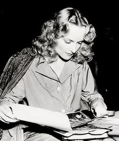 Carole Lombard, looking at photo's