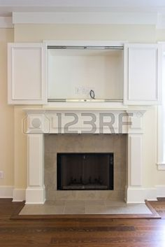 adding cabinet doors is a great idea to hide the annoying space above the fireplace.