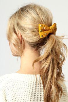 Peinado con coleta deshecha y lazo en el pelo con tachuelas