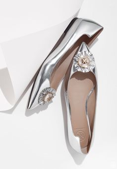 Like jewelry for the feet, our Melody Flat is decorated with a logo-accented pearl encircled with a ruffle. An elongating silhouette, done in metallic silver leather, it has a pointed toe and an elega