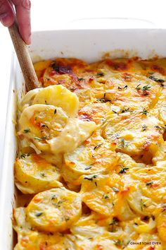 Scalloped Potatoes With Butter, Yellow Onion, Large Garlic Cloves, All-purpose Flour, Chicken Stock, Milk, Kosher Salt, Black Pepper, Fresh Thyme Leaves, Yukon Gold Potatoes, Sharp Cheddar Cheese, Grated Parmesan Cheese