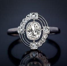 An Art Deco Diamond and Platinum Vintage Engagement Ring. The unusual asymmetrical design of this engagement ring was clearly influenced by the Russian avant garde art of the 1920s-1930s. The ring features a bezel-set old cushion-cut diamond in an openwork frame embellished with old rose-cut diamonds.
