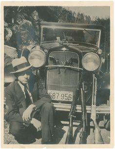 Clyde Barrow posing in 1933 in front of his beloved Ford, with a rifle and two shotguns leaning against the front, two revolvers tucked into the grill and one hanging from the hood ornament. Bonnie Clyde, Bonnie And Clyde Photos, Bonnie Parker, Vintage Photographs, Vintage Photos, Old Photos, Vintage Art, Baby Face Nelson, Real Gangster