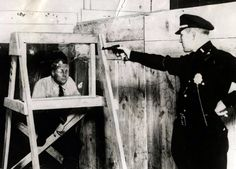 Testing bullet proof glass - 1931 -- like we wouldn't know if it was bulletproof without the Darwin Award contestant sitting behind it? Or did the marketing department put him up to it for testimonial advertising?