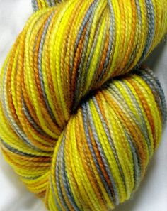 """Meta-Crisis - Inspired by the Human/Time Lord Meta-Crisis of Donna Noble in Doctor Who, this colorway is kettle dyed in yellows, golds, and silver on a sparkle yarn. Shown here on Astral which is a gold sparkle but also available on any sparkle base."""