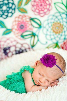 Cute backdrop and headband on newborn girl. Fun colors.