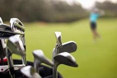 A bag of golf clubs sits on the course while a young Asian female golfer takes a swing in the background - Noel Hendrickson/Digital Vision/Getty Images