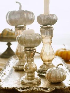 A simple display of mini pumpkin gourds can rise to the occasion as stylish centerpiece just by adding a little height. Perch pumpkins atop overturned bowls, cake plates or candlesticks are perfect for creating an interesting display.  Try painting the pumpkins in metallic silver for a sophisticated, glitzy effect