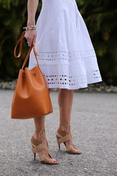 Orange bucket bag, camel lace-up heels, and a white eyelet-trim dress | See more about lace up sandals, full circle skirts and circle skirts.