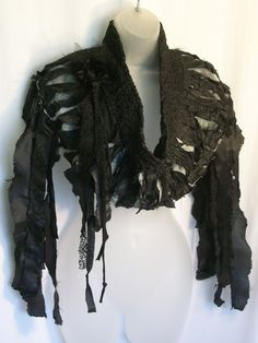 This black capelet is tattered and shredded, on purpose!!! The neck is high in the back and tapers down in the front~ kind of resembling a cowl neck. There are tattered bits and pieces attached to the sides of the cape which hang down at your sides which swing and sway as you walk. There is a flower on the right hand lapel which I have made out of frayed satin, tulle and a tiny grey button as shown in the fourth picture; they are the same buttons that are on the back of the neck. ( shown in…
