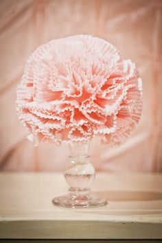 Adore this! it s a sweet and frilly paper pom pom made out of a styro ball and cupcake liners! could add even more finesse to it by adding big pearl-topped pins into the centre of some of the cupcake liners.   Love it atop a curvy glass vessel.