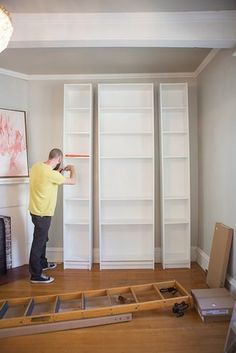 Ikea Billy Bookcases ($40-$60) of various sizes are assembled together to create the three columns of the built-ins.