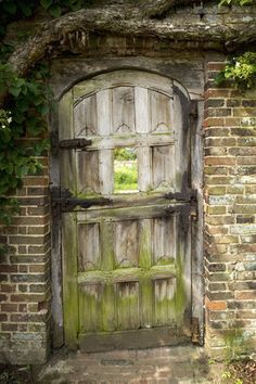 Charming old wooden gate leading to the garden from  Barrington Court Mansion, Somerset, England.