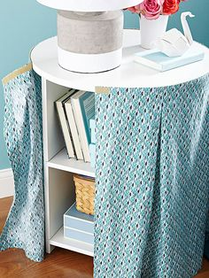 Not all items to be stored need be in view. Furniture tricks -- here, a table skirt with a pretty pattern -- help to hide shelves, baskets, and the like for a clean look that still boosts storage.