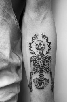 skeleton with laurel leaves black and white forearm tattoo