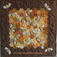 """Quilting Bees, 12 1/2"""" square by Karen H. ~ """"I used 1/2"""" hexagons. I basted my hexagon papers to various honey colour scraps of fabric and stitched them together. Once it was pieced I gave it a spritz of starch and a good press with a hot, dry iron. The basting threads and papers were removed. I cut a piece of brown fabric and appliqued the honeycomb to the background. I trimmed away the excess brown fabric underneath the honeycomb."""""""