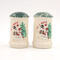 "Pre-owned salt and pepper shakers set.  Gloss glazed porcelain ceramic shakers have green and white speckled tops with a snowman family and Christmas tree design on one side with ""Let it Snow!"" above the snowmen."