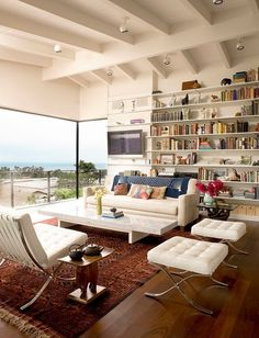 Busier bookshelves & color pops work thanks to muted furniture tones & spectacular wall of glass (with equally amazong view)