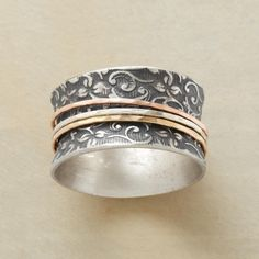 "ETERNALLY YOURS RING -- Three slender rings—sterling silver, 14kt rose gold and 14kt yellow gold— spin about an oxidized sterling silver band patterned with scrolling leaves. Whole sizes 5 to 9. 1/2""W. This ring is licensed under U.S. Patent Nos. 6,497,117 and 6,395,732.                                                                                                                                                                                 More"