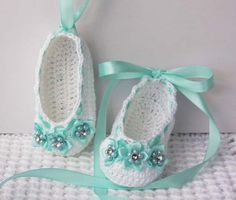 Crochet baby ballerina slippers in white with soft teal accents - Adorned with mini ribbon flowers that have pearls and rhinestone at center - Also embellished with teal satin ribbon that can be laced up baby's leg (