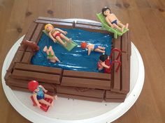 Swimming pool cake using blue butter icing, kitkats and Playmobil charachters.