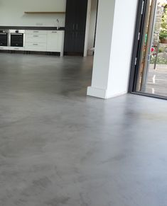Light grey kitchen floor finished in micro-cement topping. - Light grey kitchen floor finished in micro-cement topping.