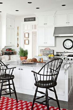 A Dash of Color Windsor stools and a red-patterned rug sit in front of the kitchen's island in this Pennsylvania home. Boat hardware takes a supporting role as kitchen cabinet latches.