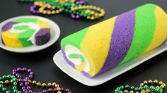 A brightly colored purple, yellow, and green striped cake roll filled with fluffy white frosting. Perfect for Mardi Gras!
