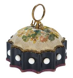 """BIEDERMEIER ERA VIENNESE PINCUSHION WITH NEEDLEWORK DESIGN 5"""" (13 cm.) diam. The round pincushion with scalloped edging and ebony frame trimmed with large white glass beads has a needlework cushion with floral design,and circle loop gilt handle with thimble hook.  Vienna,circa 1840."""