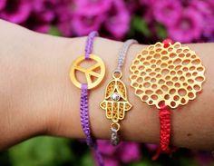lila, grau und rot geknüpfte Armbänder mit Symbolen in der Mitte.