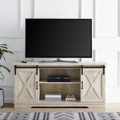 This TV stand will give your living room a charming country feel, while also providing plenty of storage space for your electronics and décor. Featuring two sliding barn door styled cabinet fronts for a versatile design where you can either close off the middle or both sides, depending on your needs. Adjustable shelving and cable management make it simple for you to keep your electronics in one place. This media console is constructed of high-grade MDF. The modern farmhouse style of this ...