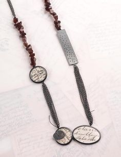 Mixed elements necklace |oxidised silver, postcards, garnets, perspex, gold | by Clare Hillerby