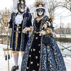 Annecy, France, February 23, 2013: Couple disguised in beautiful costumes posing near a canal in Annecy, France,  during a Venetian Carnival.
