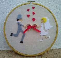 Bastidor porta alianzas, realizado en tela en color beig, con bies de color amarillo dorado. Novio y novia unidos por las alianzas que van atadas con cinta de color rojo. En la parte de abajo se puede poner la fecha de la boda.